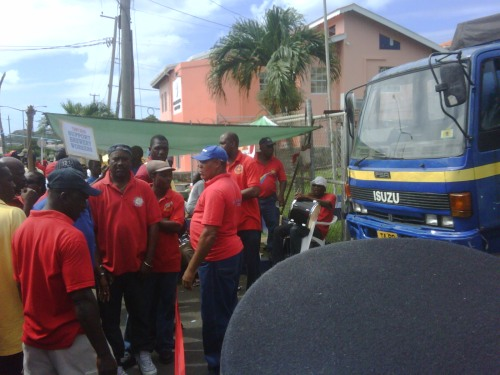 Workers block the entrance to the Grenada Breweries Factory, preventing delivery trucks from leaving