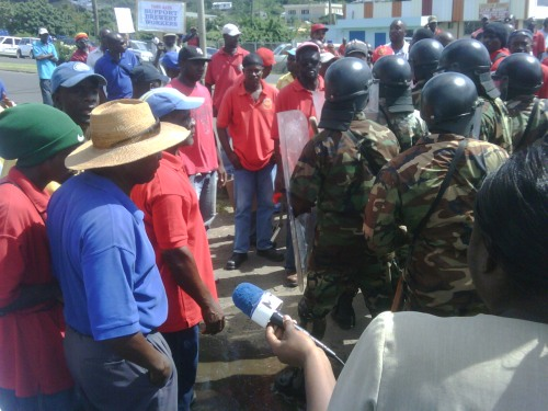 Protesters and Riot Police in confrontation in front the factory of the Grenada Breweries