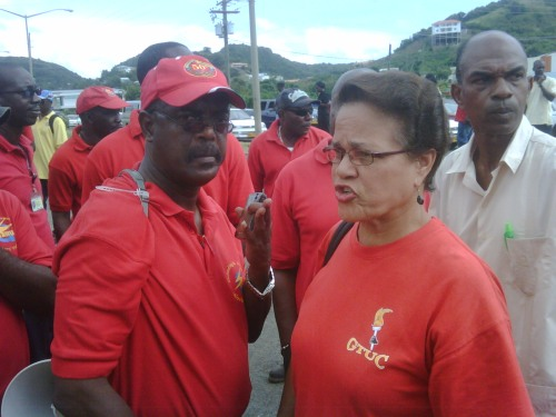 Madonna Harford and Chester Humphrey in conversation at the entrance to the Grenada Breweries with President of the Commercial and Industrial Workersr Union George Mason listening in